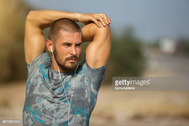 Young male athlete stretching his arm on road