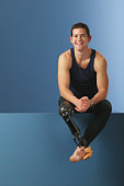 Young male athlete with prosthetic leg, smiling, portrait