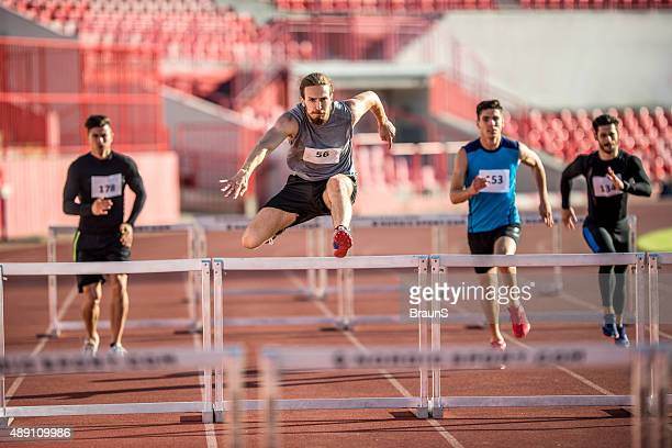 Young male athletes jumping hurdles on a sports race.