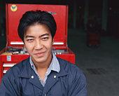 Young male automotive shop student smiling, close-up, portrait