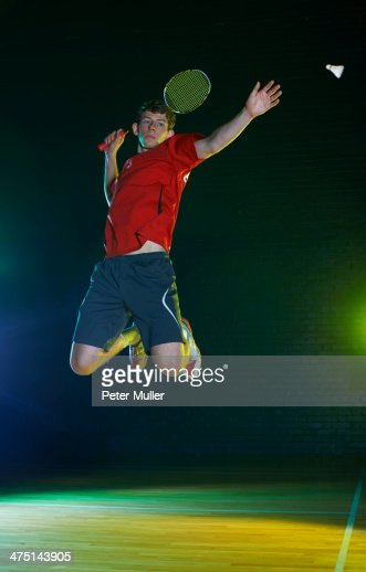 Young male badminton player mid air on court