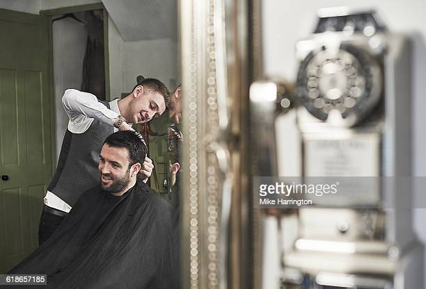 Young male barber cutting hair