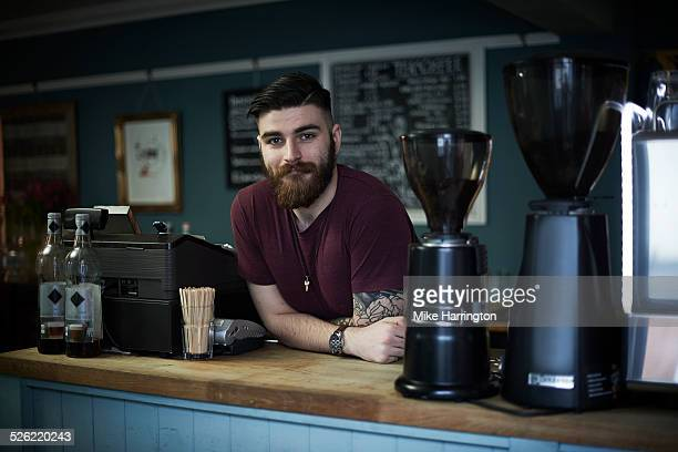 Young male barista in urban cafe