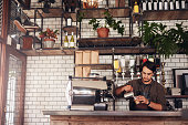 Indoor shot of young male barista making a cup of coffee while standing behind cafe counter. Young man pouring milk into a cup of coffee.