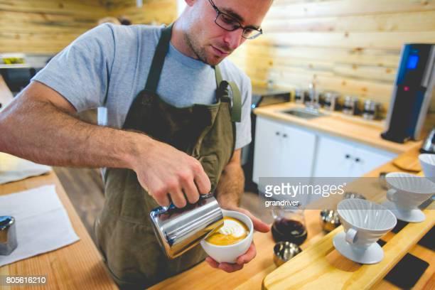 Jeune Barista mâle faisant une Latte