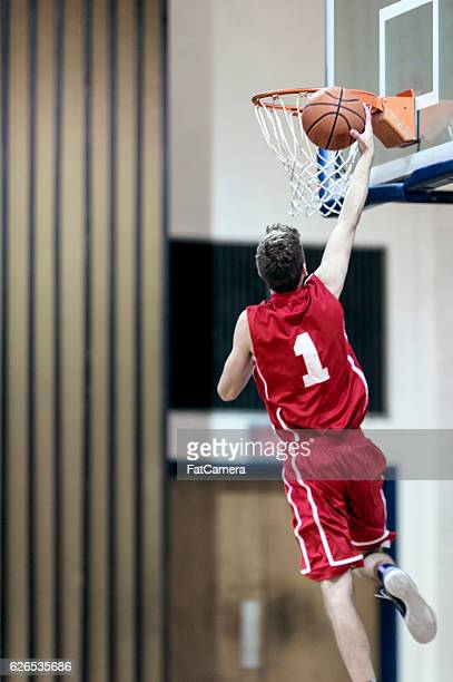 Young male basketball player attempting a dunk