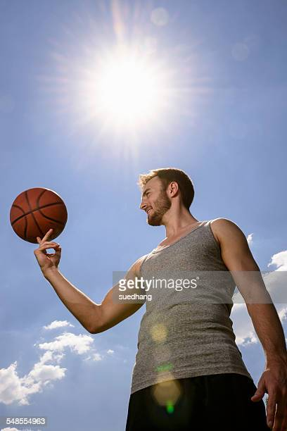 Young male basketball player balancing and spinning ball on finger