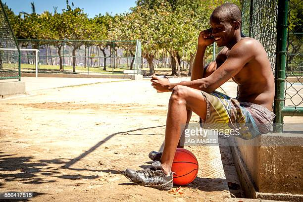 Young male basketball player chatting on smartphone and drinking water