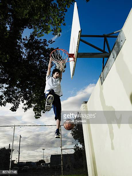 Young male basketball player hanging from rim, scr