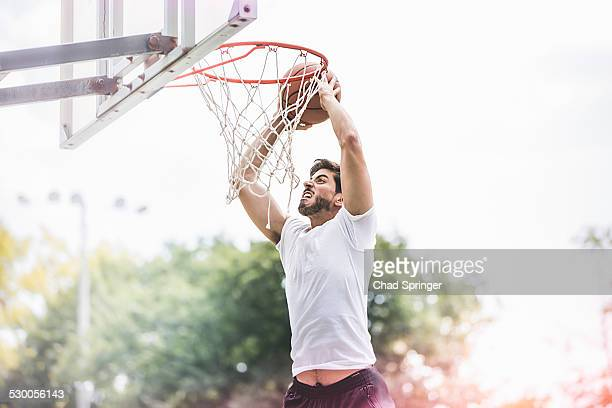 Young male basketball player jumping with ball to score