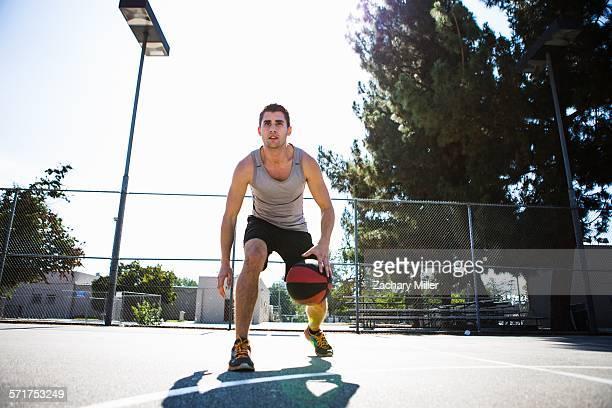 Young male basketball player preparing to throw ball on basketball court
