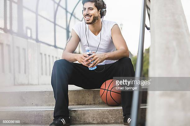 Young male basketball player sitting on footbridge listening to headphones