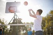 Young male basketball player throwing basketball into hoop