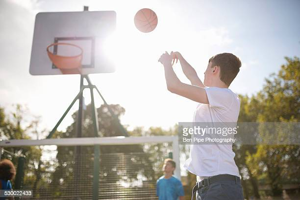 Young male basketball player throwing basketball into hoop
