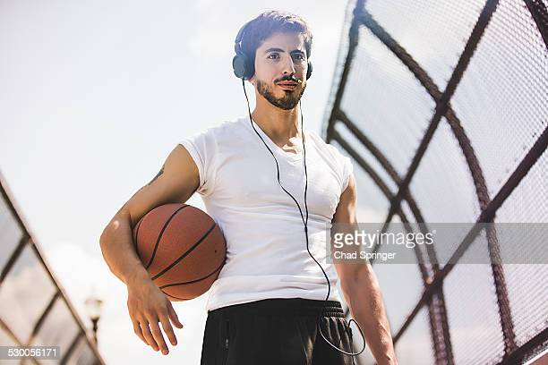 Young male basketball player walking along footbridge listening to headphones