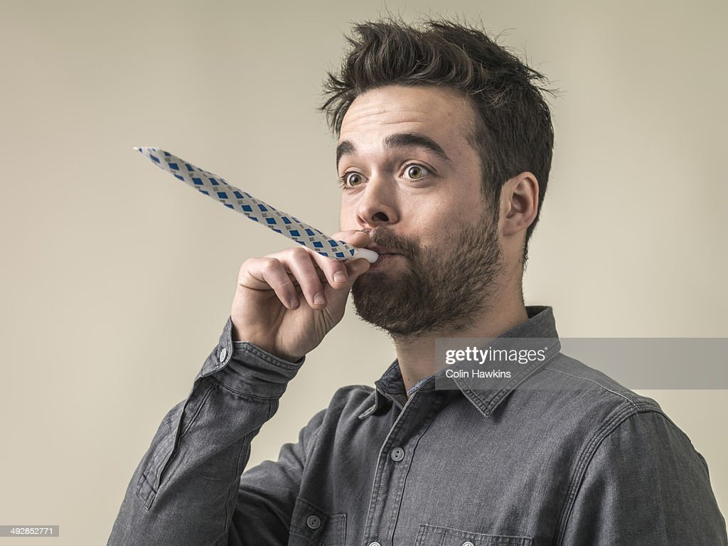 Young male blowing party horn : Stock Photo