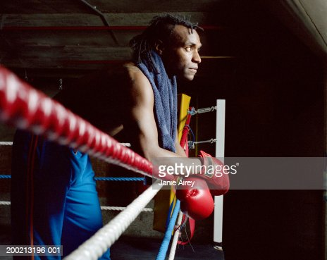 Young male boxer arms crossed resting on ring side, looking ahead : Stock Photo