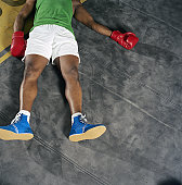 Young male boxer lying on back on floor, overhead view