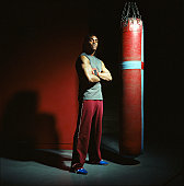 Young male boxer standing by punch bag, arms crossed, portrait