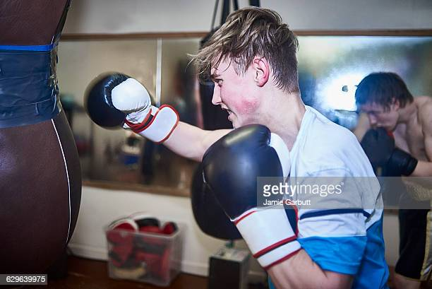Young male boxer training on a punch bag