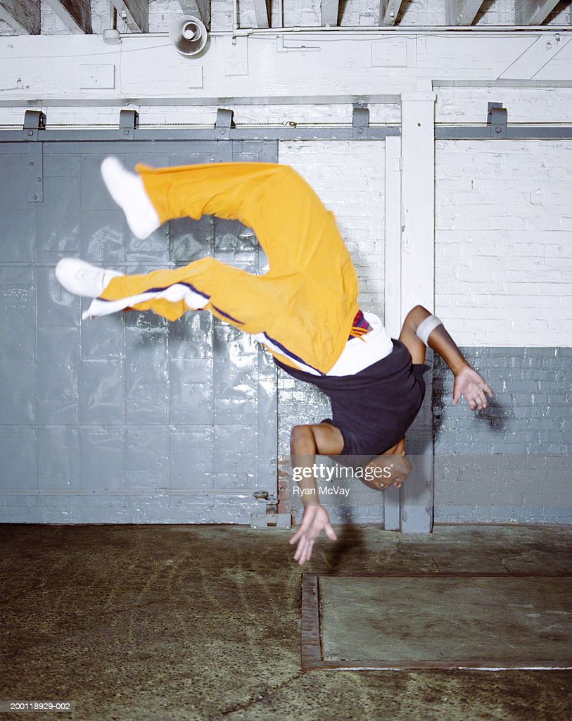 Young male breakdancer doing backflip (blurred motion) : Stock Photo