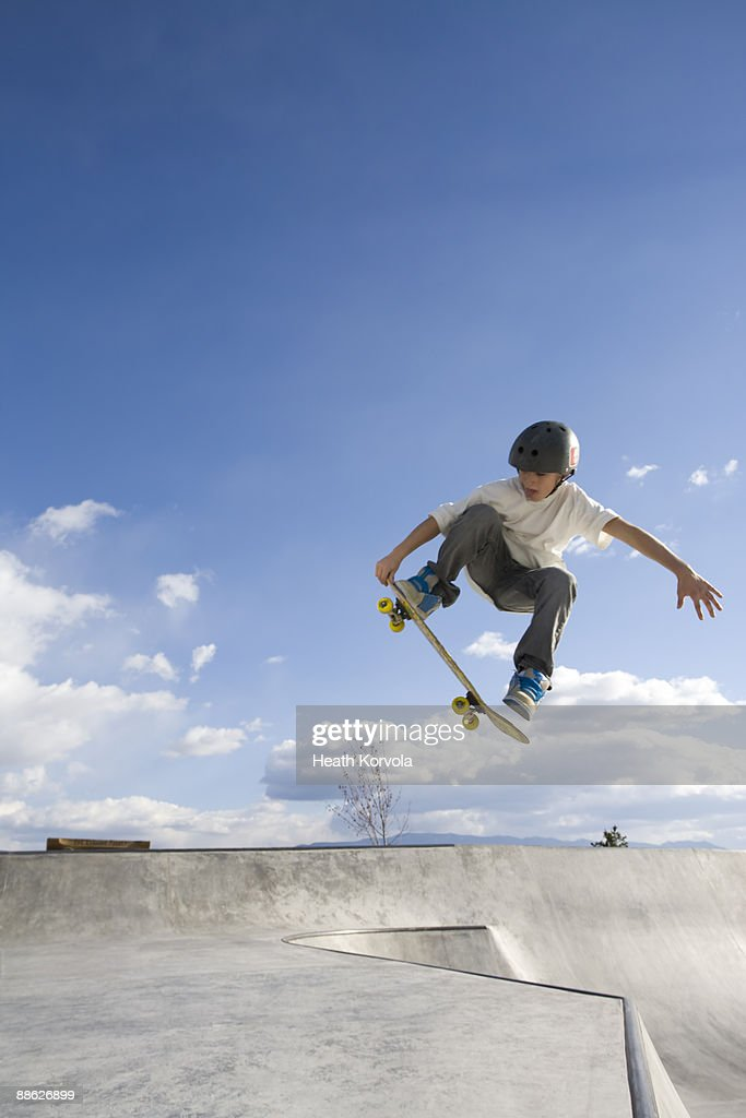 A young male catches some air in a skate park. : Stock Photo