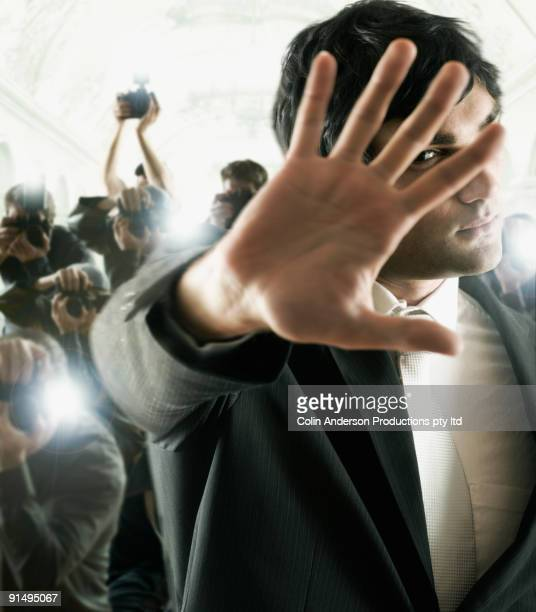Young male celebrity shielding face from photographers