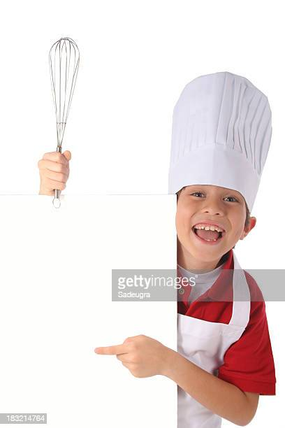 A young male chef holding a whisk and point at a blank menu