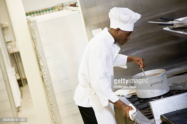 Young male chef stirring food in pot on stovetop, side view