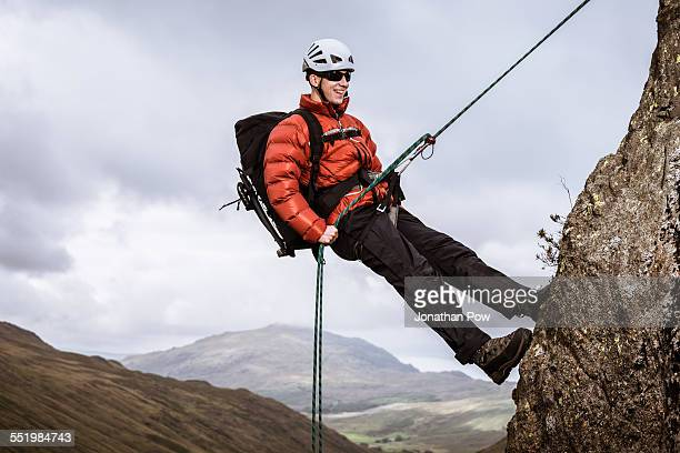 Young male climber abseiling down rock, The Lake District, Cumbria, UK