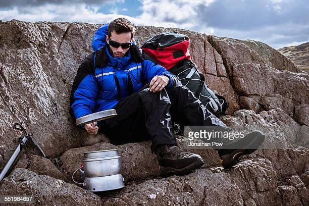Young male climber on rock preparing camping stove, The Lake District, Cumbria, UK