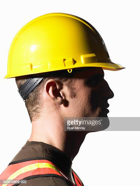 Young male construction worker wearing hardhat, side view