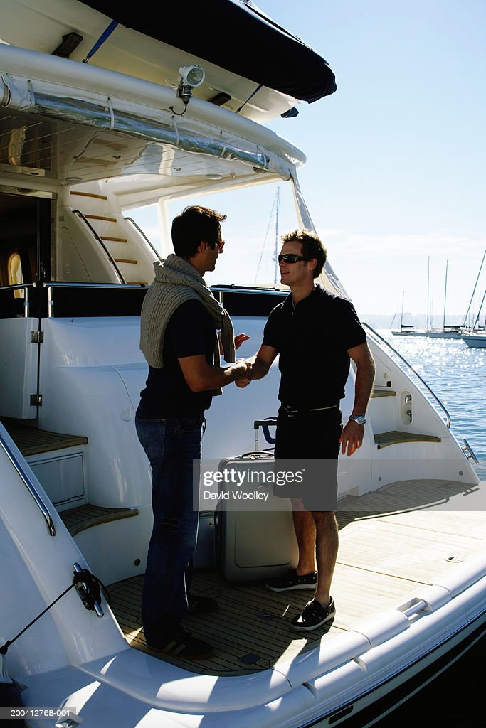 Young male crew member greeting man on board yacht, smiling : Stock Photo