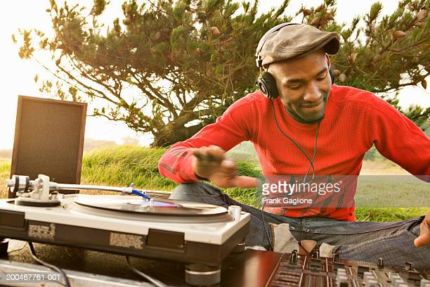 Young male DJ spinning records on lawn in park, sunset