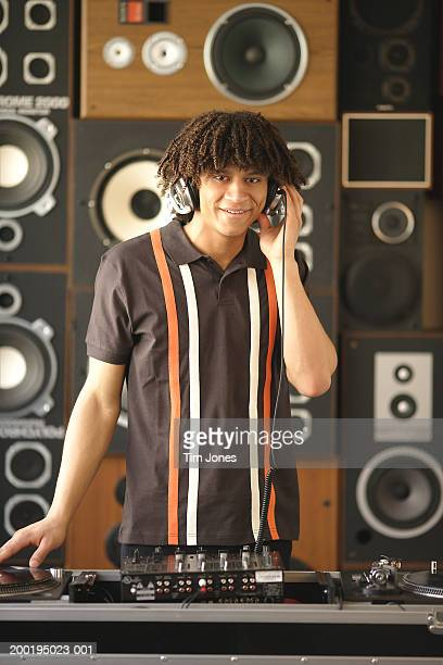 Young male DJ spinning records, wearing headphones, portrait