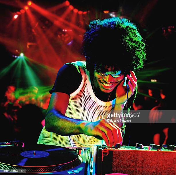 Young male DJ using record decks in nightclub