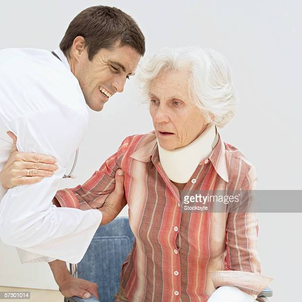 Young male doctor helping an elderly woman out of a wheelchair