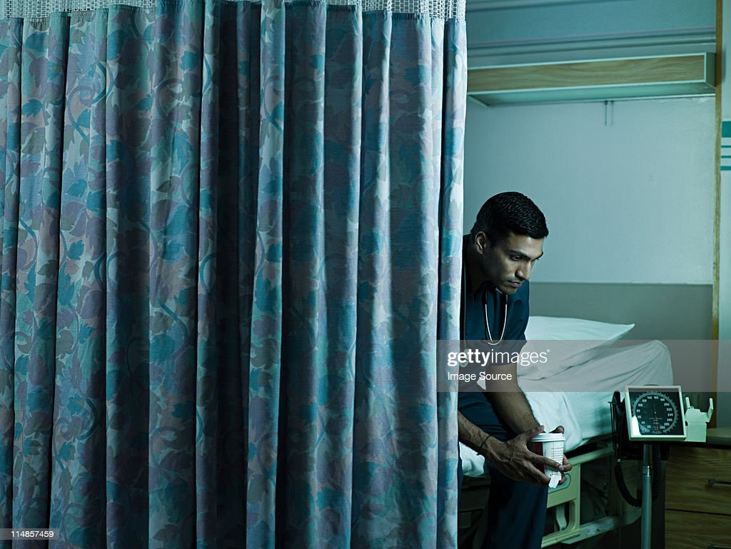 Young male doctor sitting on hospital bed : Stock Photo