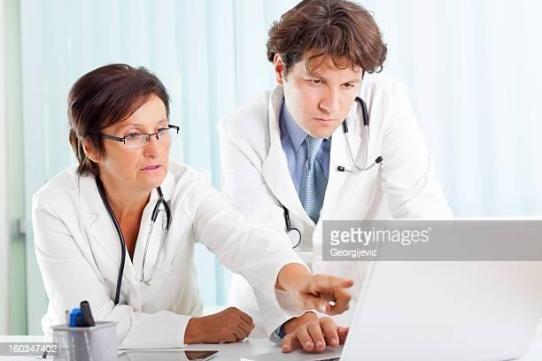 Jungen männlichen Arzt mit senior weiblichen Kollegen