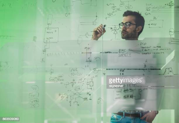 Young male engineer drawing a diagram on a glass wall.