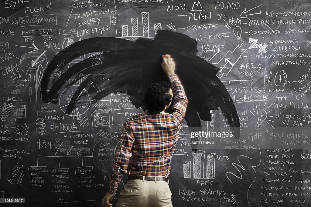 Young male erasing business plans on blackboard : Stock Photo