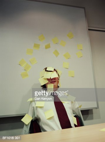 Young male executive covered with adhesive notes : Stock Photo