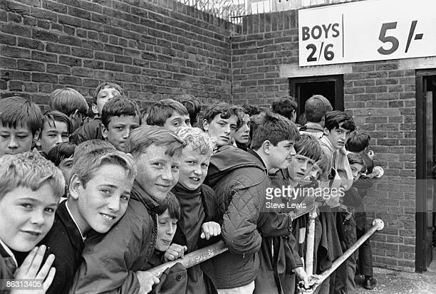 Young male fans waiting to get into West Ham football club in the East End of London through the 'Boys' entrance 1960s