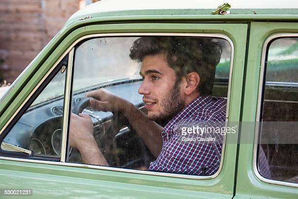 Young male farmer looking out of car window, Premosello, Verbania, Piemonte, Italy