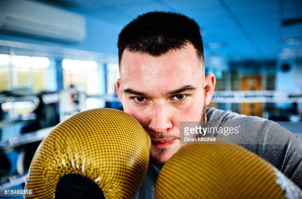Young male fighter with raised hands in gloves at fight club