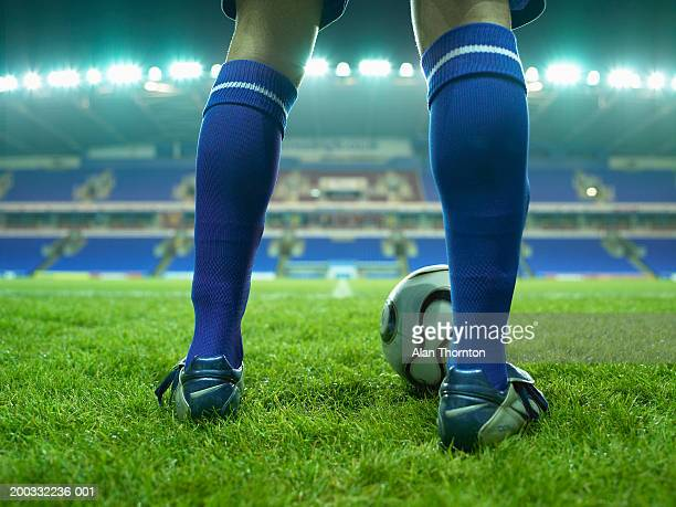 Young male football player on pitch, low section, night