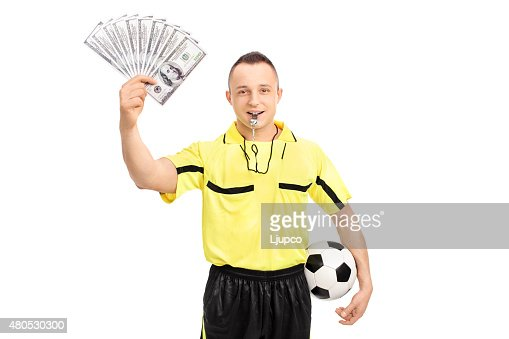 Young male football referee holding a stack of money : Stock Photo
