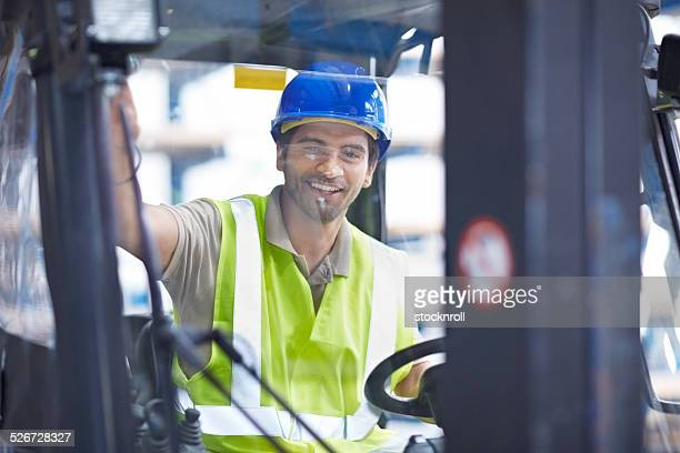 Young male forklift driver at distribution warehouse
