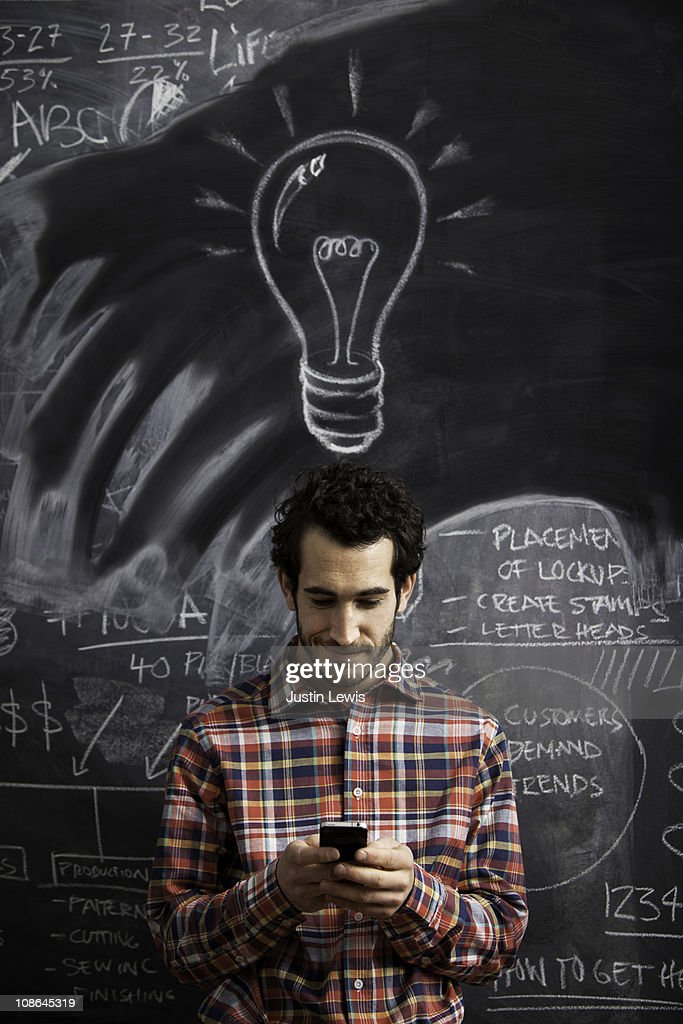 Young male getting an idea and sending message : Stock Photo