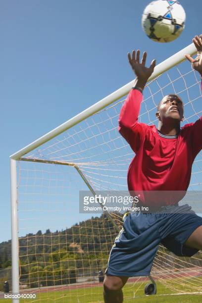 Young male goal keeper jumping to catch the ball